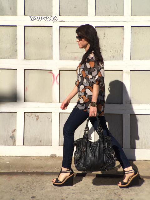 Fashionable Brunette Walking By Downtown Los Angeles Industrial Garage Door In Black Wedges