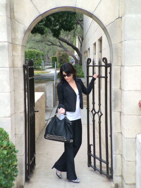 Brunette In Black Leather Jacket And Blue Jeans Modeling Black Leather Bag And White Leopard Print Pumps